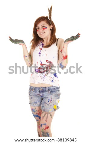 A woman all covered in paint with her hands up smiling.