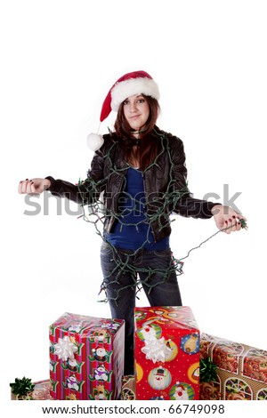 a woman all tied up in a bunch of Christmas lights by her presents with a frustrated expression on her face.