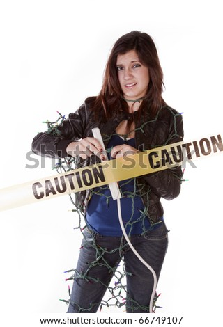 a woman all tied up in a bunch of Christmas lights not sure she wants to plug them in with a frustrated expression on her face.