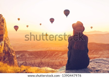 A woman alone unplugged sits on top of a mountain and admires the flight of hot air balloons in Cappadocia in Turkey. Digital detox and soul search Foto stock ©