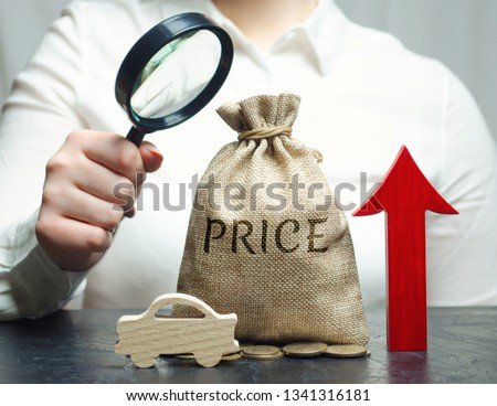 A woman analyzes the prices for the purchase of vehicles. The cost of auto maintenance is increasing. High interest rates for buying a car on credit. Insurance and automobile repair. Magnifying glass