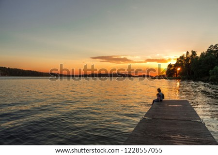 A woman and a little girl are sitting on the pier with their bare feet dangling in the lake. The union of mother and daughter. Beautiful sunset background with warm soft light.