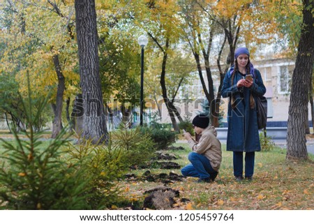 A woman and her child taking pictures on a mobile phone of a small tree in the Park in the fall.