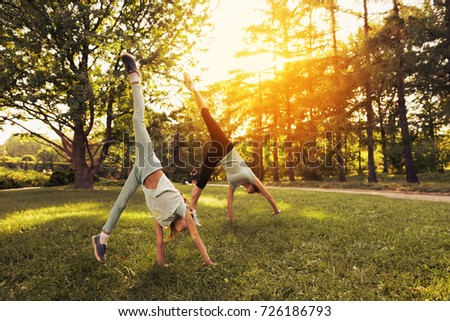 A woman and her daughter are doing a handstand in the park. They are engaged in gymnastics