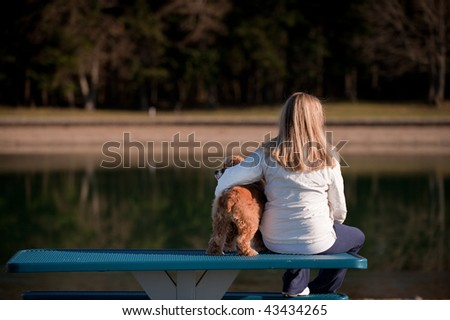 A woman and her dog on a bench by a lake