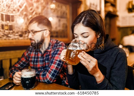 A woman and her friends try freshly brewed authentic Czech beer in a tavern in Prague