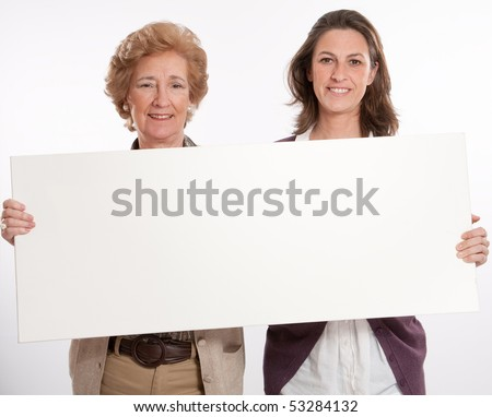 A woman and her mother holding a blank message board ideal for inserting your message