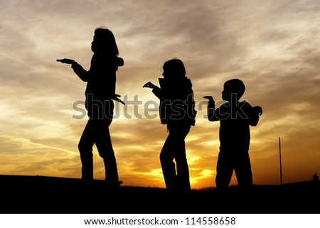 A woman and her two children play around during sunset.