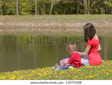 a woman and her young boy child go fishing at the pond