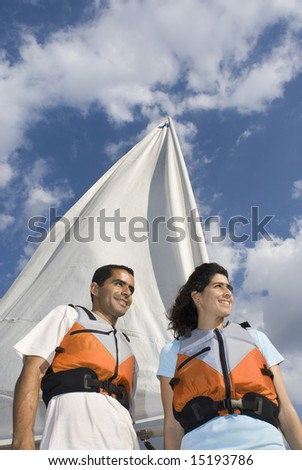 A woman and man are next to a sailboat.  They are smiling and looking away from the camera.  Vertically framed shot.