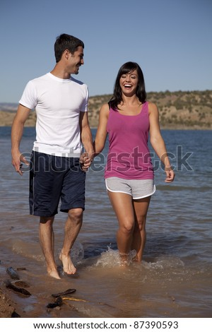 A woman and man holding hands walking in the water smiling and laughing.