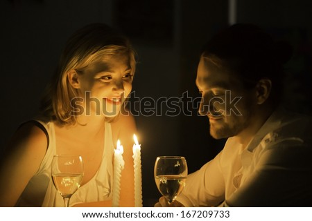 A woman and man share a joke over a glass of white wine at a candle lit table.