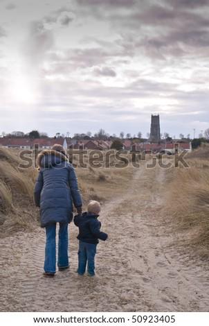 A woman and son walk down an English country path towards a village church