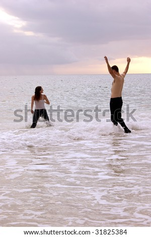 a woman appears to be running into the ocean followed by a tall man, shirtless with his arms up, they are playing in the water at sunset.