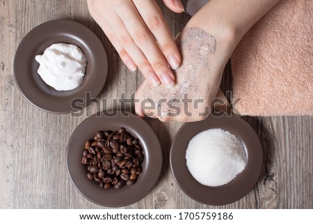A woman applies a natural coffee scrub to the skin. Homemade scrub made of sugar, salt, cream and coffee. Beauty, Spa, skin care, aromatherapy. Moisturizing, peeling, exfoliation