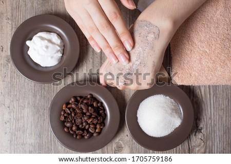 A woman applies a natural coffee scrub to the skin. Homemade scrub made of sugar, salt, cream and coffee. Beauty, Spa, skin care, aromatherapy. Moisturizing, peeling, exfoliation