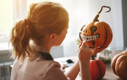 a woman artist prepares for halloween and paints pumpkins