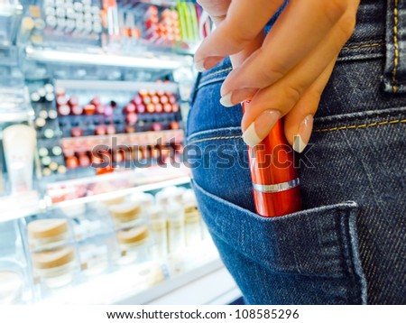 a woman as a shoplifter. steals a lipstick in the cosmetics department of a department store.