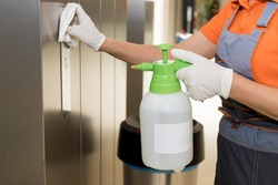 A woman at work wearing gloves. A professional cleaner cleans the business center. Sterilization of walls and Elevator in the shopping center.
