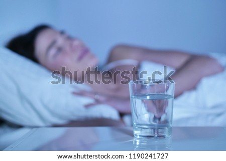 A woman before going to bed takes medication to treat her symptoms of illness such as headaches, stomach ache and flu. Concept of: illness, wellness, medicines and pharmacy