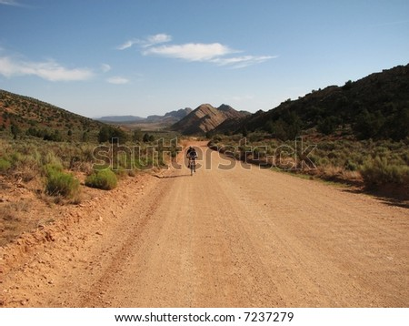 a woman bicycles along a dirt road in the middle of nowhere with copy space in the roadbed