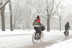 A woman biking in the Amsterdam Vondelpark on a snowy winter day in december in the Netherlands.