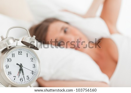A woman blocks her ears with a pillow as her alarm clock goes off.
