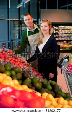 A woman buying fruit and vegetables at a supermarket, receiving help from a grocer