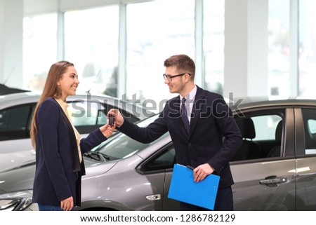 A woman buys a car from salesman in the auto salon