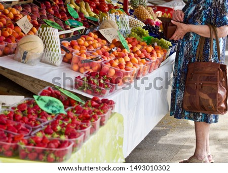 a woman buys a lot of fruits at a market