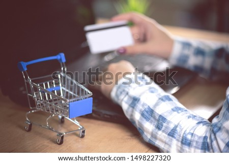 A woman buys goods in online store. Female hands is holding a credit card on a laptop background.