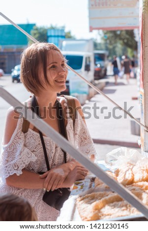 A woman buys pies at a street cafe in the summer.