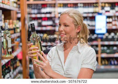 a woman buys wine in a supermarket. wine rack with wines from around the world.