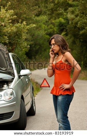 A woman calls for assistance using her mobile phone, after her car broke down on the road side