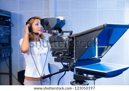 a woman cameraman at a TV studio during live broadcasting