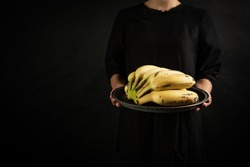 A woman carried a basket of bananas in her hand on black background.