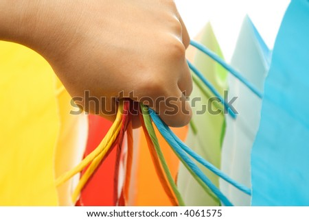 A woman carrying a bunch of colorful shopping bags