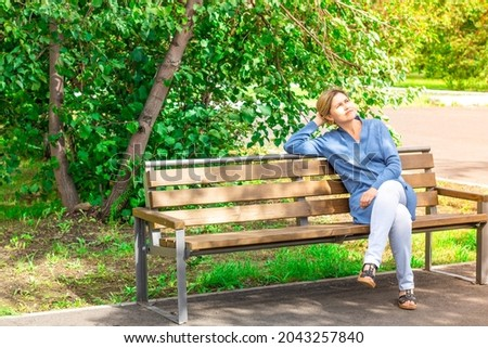 A woman catches the last warm days and the sun's rays at the end of summer before the arrival of aut. A woman sits on a bench basking in the sun in the park. Cool summer day before fall. caucasian. Stock fotó ©