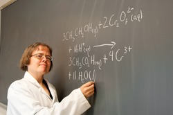 A woman chemistry instructor writes out a chemical equation on a chalk board. The equation describes the chemistry behind the