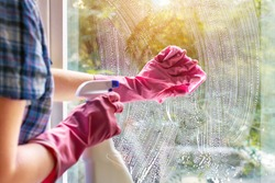 A woman clean a window pane with a rag and soap suds. Cleaning with a detergent. Hands in pink protective gloves washing glass on the windows of the house with a spray bottle, home routine concept.