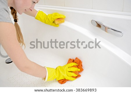 A woman cleaning bath at home. Female washing bathtub in yellow rubber gloves with orange sponge - housework, spring cleaning concept #383669893