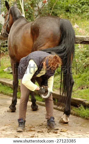 A woman cleans a  hoof of horse.