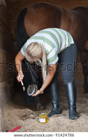 A woman cleans a hoof of horse