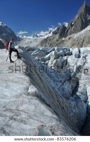 A woman climber considers her options crossing a crevasse field on the 'sea of ice' or mer de glace in the mont blanc massif above Chamonix, France - stock photo