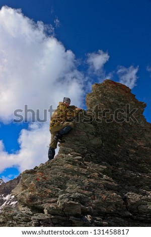 A woman climbs a cliff. Against the background of clouds and blue sky - stock photo