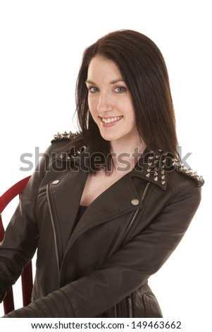 A woman close in a leather jacket smiling.