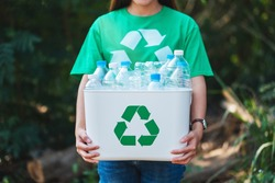A woman collecting garbage and holding a recycle bin with plastic bottles in the outdoors