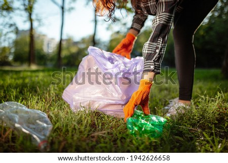 A woman collects and puts used plastic bottle into a trash bag. A volunteer cleans up the park on a sunny bright day. Clearing, pollution, ecology and plastic concept ストックフォト ©