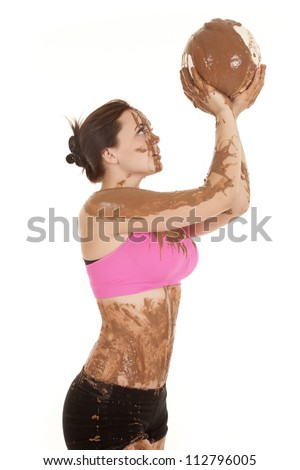 A woman covered in mud with a volleyball covered in mud.