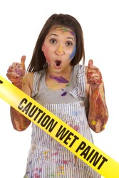 A woman covered in paint with her thumbs up at the wet paint sign.